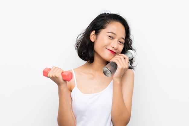 Junges asiatisches mädchen, das gewichtheben und mit einer flasche wasser macht Premium Fotos