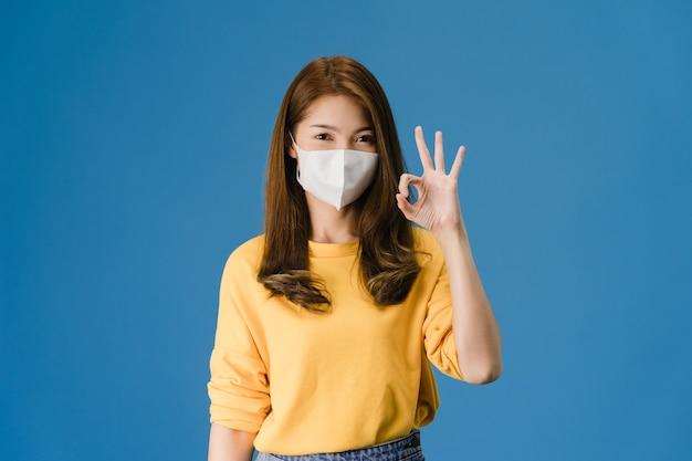 Junges asiatisches mädchen, das medizinische gesichtsmaske trägt, die ok zeichen mit gekleidet in lässigem stoff und blick auf kamera lokalisiert auf blauem hintergrund gestikuliert. selbstisolation, soziale distanzierung, quarantäne für coronaviren. Kostenlose Fotos