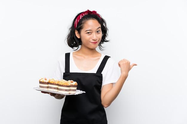 Junges asiatisches mädchen, das viele muffinkuchen über der lokalisierten weißen wand zeigt auf die seite hält, um ein produkt darzustellen Premium Fotos