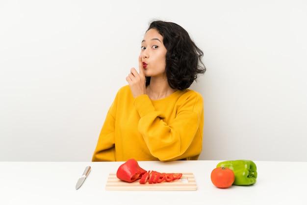 Junges asiatisches mädchen mit gemüse in einer tabelle, die ruhegeste tut Premium Fotos
