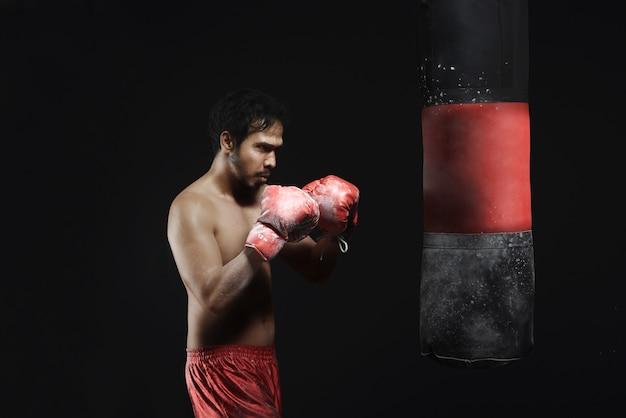 Junges asiatisches mannboxtraining mit sandsack Premium Fotos