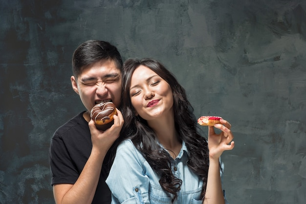 Junges asiatisches paar genießt das essen des süßen bunten donuts auf grauem studiohintergrund Kostenlose Fotos