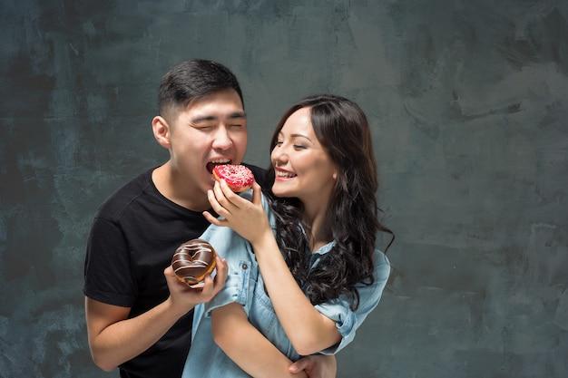 Junges asiatisches paar genießt das essen des süßen bunten donuts Kostenlose Fotos