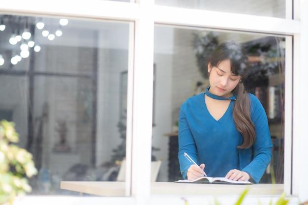 Junges asien-verfasserinschreiben des schönen porträts auf notizbuch Premium Fotos