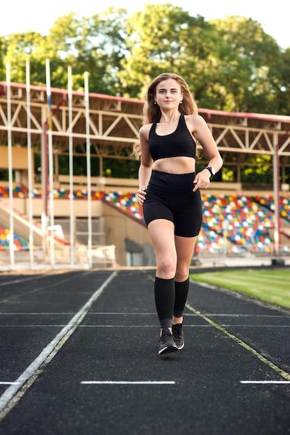 Junges, athletisches mädchen, das auf der strecke läuft Premium Fotos