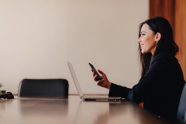 Junges attraktives emotionales mädchen in der geschäftsart kleidung, die an einem schreibtisch an einem laptop und an einem telefon im büro oder im auditorium sitzt Premium Fotos