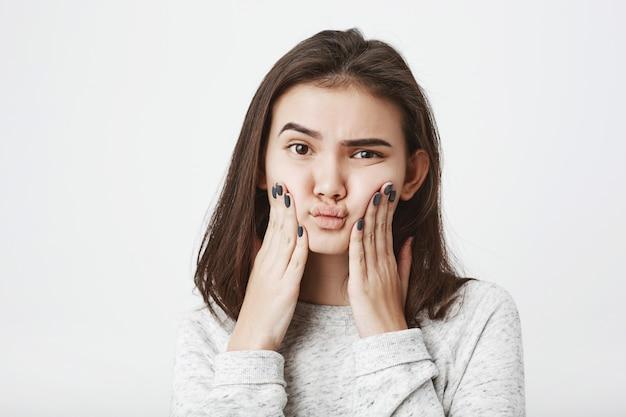 Junges attraktives europäisches weibliches modell, das ihre wangen mit verwirrtem und zweifelhaftem ausdruck drückt Kostenlose Fotos