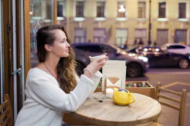 Junges attraktives mädchen, das am abend in einem café sitzt. Premium Fotos
