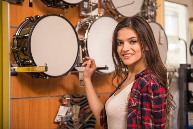 Junges attraktives mädchen wählt trommeln im musikspeicher. Premium Fotos