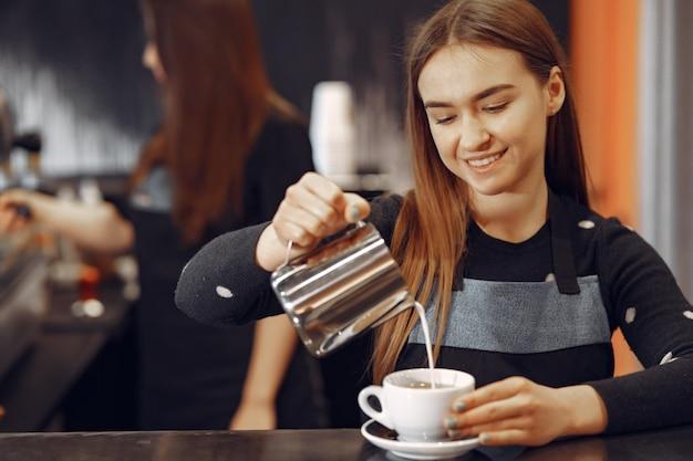Junges barista-mädchen macht kaffee und lächelt Kostenlose Fotos