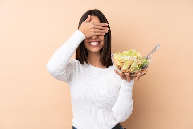 Junges brünettes mädchen, das einen salat über isolierten wandabdeckungsaugen durch hände hält. ich will nichts sehen Premium Fotos