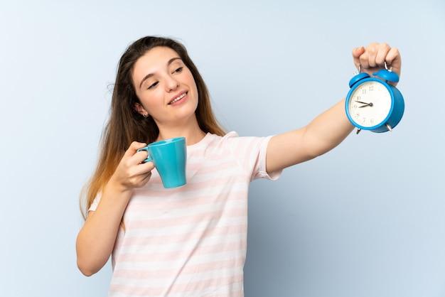 Junges brunettemädchen, das eine tasse kaffee- und weinleseuhr hält Premium Fotos
