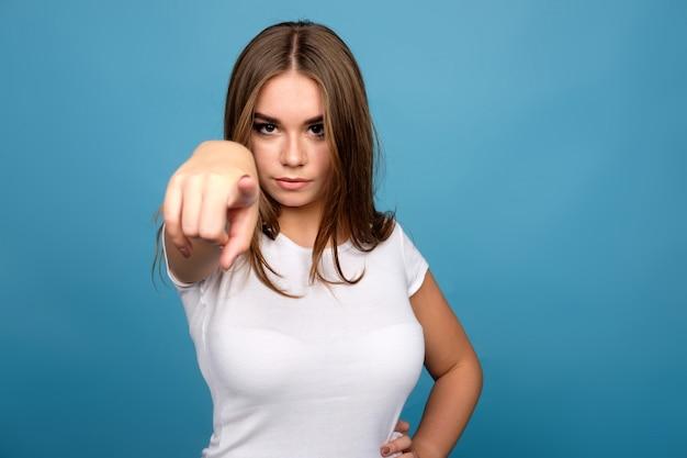 Junges brunettemädchen im weißen t-shirt vorwärts zeigend mit den zeigefingern, blauer hintergrund Premium Fotos
