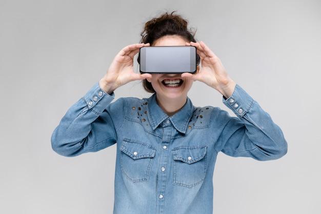 Junges brunettemädchen in den runden gläsern. haare werden in einem brötchen gesammelt. mädchen mit einem schwarzen telefon. das mädchen bedeckte ihr gesicht mit einem telefon. Premium Fotos