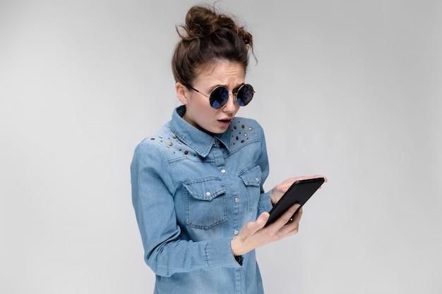 Junges brunettemädchen in den runden gläsern. haare werden in einem brötchen gesammelt. mädchen mit einem schwarzen telefon. Premium Fotos