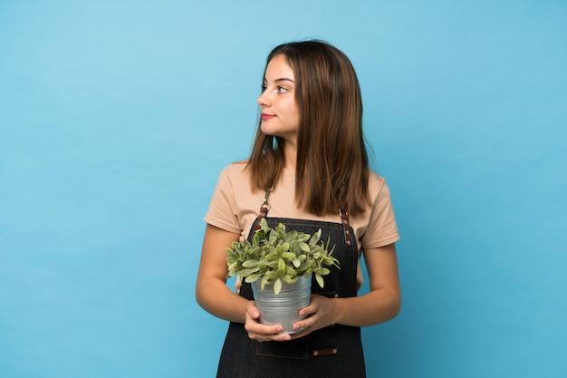 Junges brunettemädchen über dem lokalisierten blau, das einen blumentopf nimmt Premium Fotos