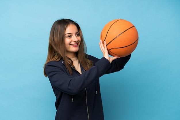 Junges brunettemädchen über lokalisierter blauer wand mit ball des basketballs Premium Fotos