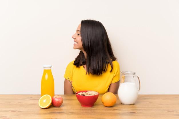 Junges brunettemädchen, welches die frühstücksmilch schaut zur seite hat Premium Fotos