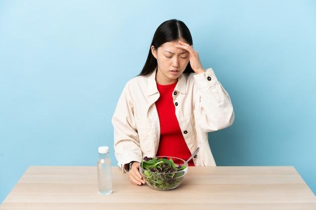 Junges chinesisches mädchen, das einen salat mit kopfschmerzen isst Premium Fotos
