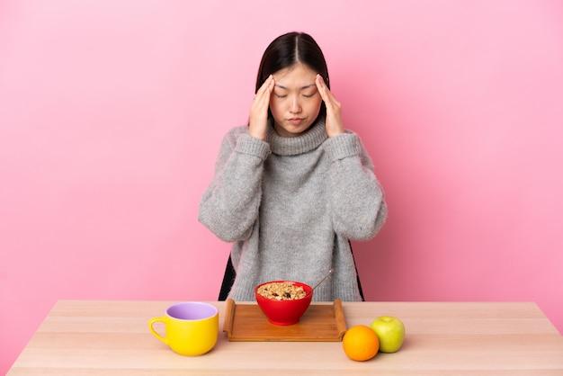 Junges chinesisches mädchen, das frühstück in einer tabelle mit kopfschmerzen hat Premium Fotos