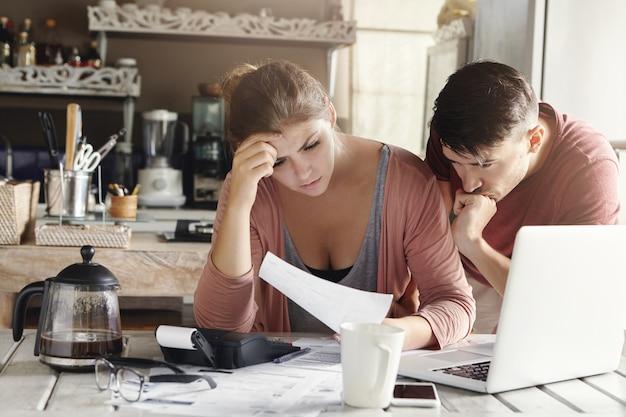Junges ehepaar mit finanziellem problem während der wirtschaftskrise. frustrierte frau und unglücklicher mann, der stromrechnung in der küche studiert, schockiert über den betrag, der für gas und strom bezahlt werden muss Kostenlose Fotos