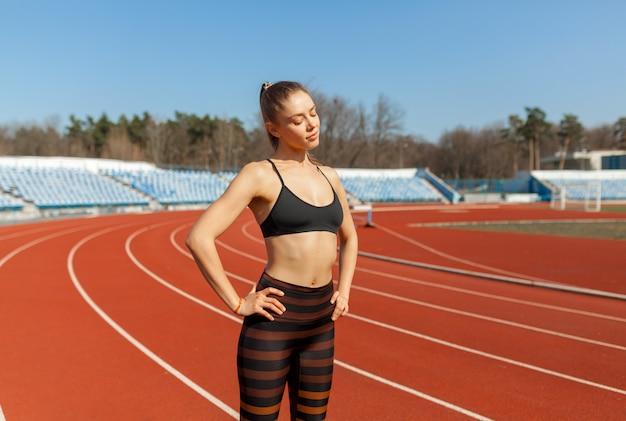 Junges eignungsfrauenläuferaufwärmen, bevor es auf spur läuft Premium Fotos