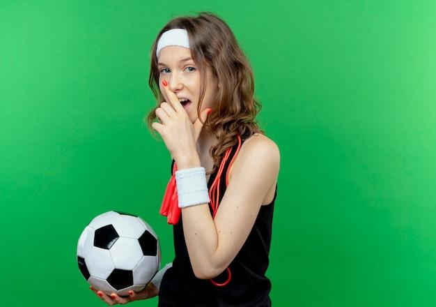 Junges eignungsmädchen in der schwarzen sportbekleidung mit stirnband und springseil um den hals hält fußball, der fröhlich über grüner wand steht Kostenlose Fotos