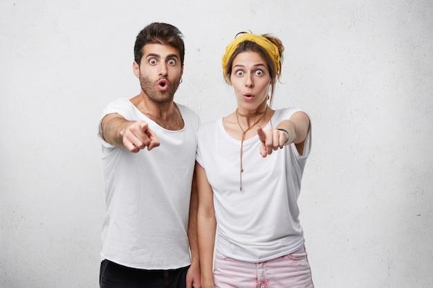 Junges erstauntes paar, das mit zeigefingern auf sie zeigt. mann und frau mit abgehörten augen, die drinnen auf etwas zeigen Kostenlose Fotos