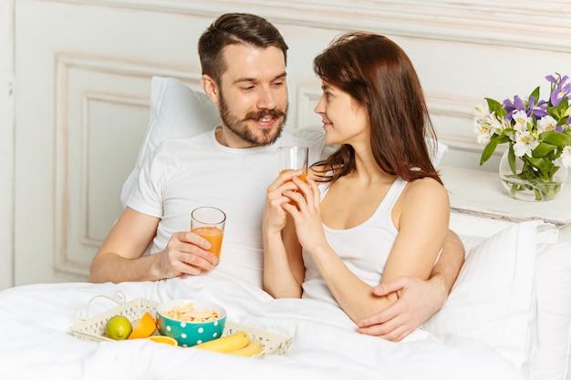 Junges erwachsenes heterosexuelles paar, das auf bett im schlafzimmer liegt Kostenlose Fotos