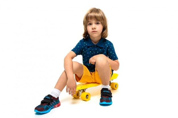 Junges europäisches niedliches kind in der sportkleidung, die auf gelbem skateboard auf weiß sitzt Premium Fotos