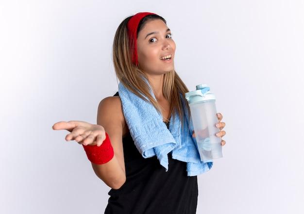 Junges fitness-mädchen in schwarzer sportbekleidung und rotem stirnband mit handtuch um den hals, das flasche wasser mit arm heraus hält, als fragend, über weißer wand stehend Kostenlose Fotos