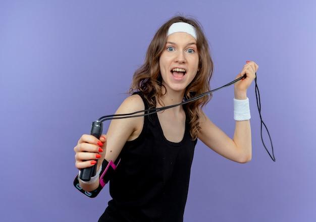 Junges fitnessmädchen in der schwarzen sportbekleidung mit dem stirnband, das das springseil glücklich und aufgeregt über der blauen wand hält Kostenlose Fotos