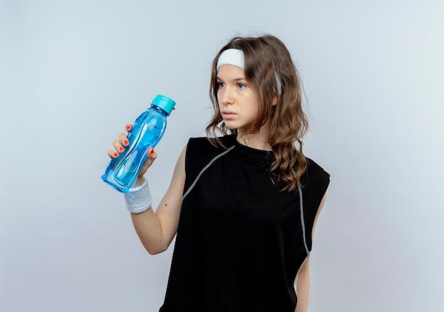 Junges fitnessmädchen in der schwarzen sportbekleidung mit dem stirnband, das flasche wasser hält, das beiseite steht, verwirrt über weißer wand steht Kostenlose Fotos