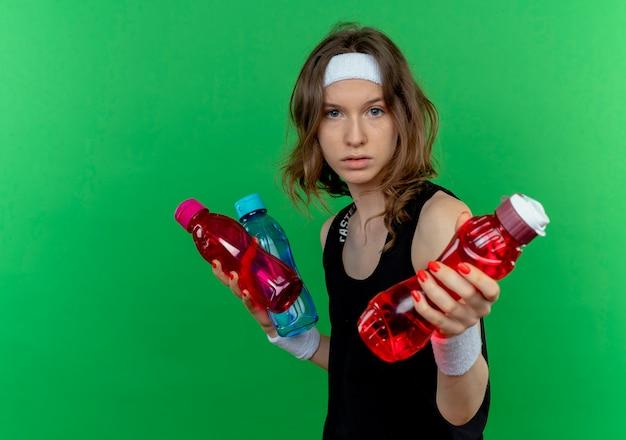 Junges fitnessmädchen in der schwarzen sportbekleidung mit dem stirnband, das flaschen des wassers hält, das eine der flaschen anbietet, die über grüner wand stehen Kostenlose Fotos