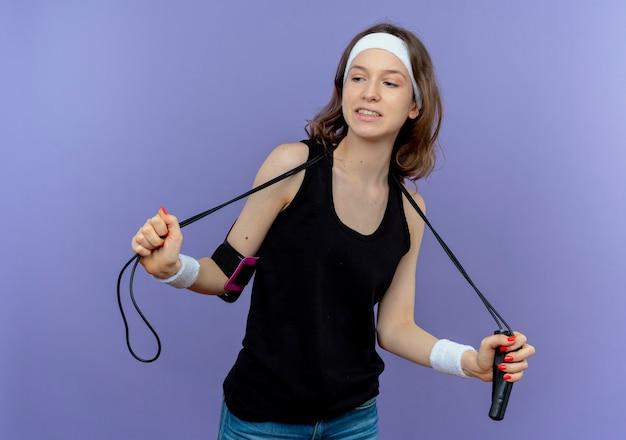 Junges fitnessmädchen in der schwarzen sportbekleidung mit stirnband, das springseil-lookign zuversichtlich über der blauen wand hält Kostenlose Fotos