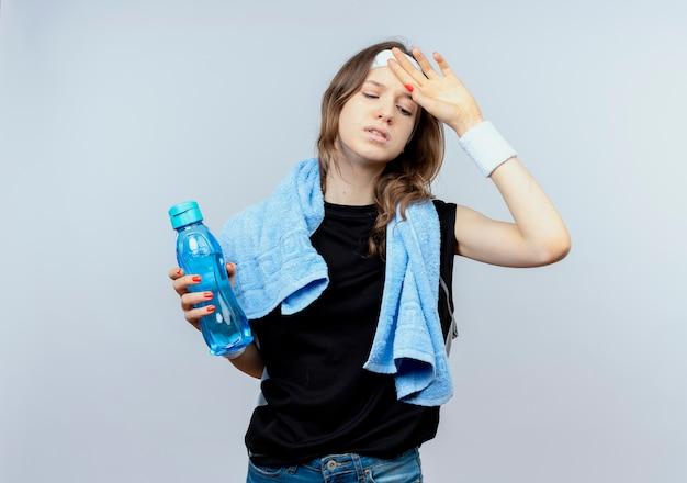 Junges fitnessmädchen in der schwarzen sportbekleidung mit stirnband und handtuch um den hals hält flasche wasser, das müde steht über weißer wand steht Kostenlose Fotos