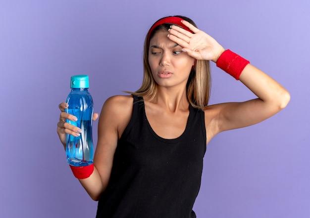 Junges fitnessmädchen in der schwarzen sportbekleidung und im roten stirnband, die flasche wasser halten, das müde und erschöpft nach dem training steht, das über der blauen wand steht Kostenlose Fotos