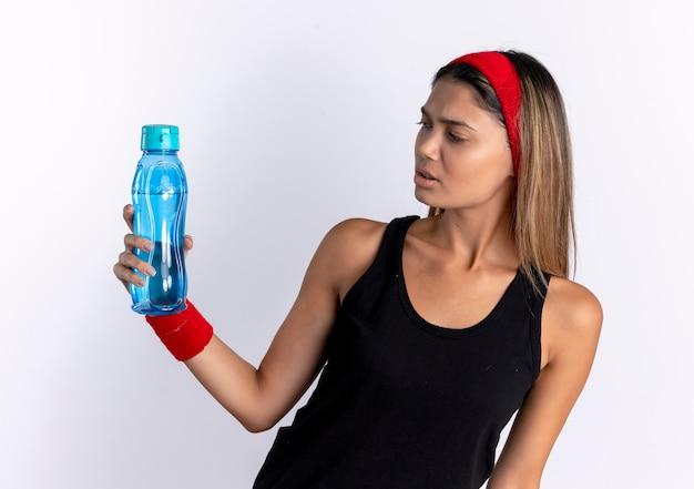 Junges fitnessmädchen in der schwarzen sportbekleidung und im roten stirnband, die flasche wasser halten, die es mit verwirrendem ausdruck betrachtet, der über weißer wand steht Kostenlose Fotos