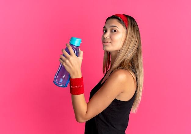 Junges fitnessmädchen in der schwarzen sportbekleidung und im roten stirnband, die flasche wasser lächelnd zuversichtlich über rosa halten Kostenlose Fotos