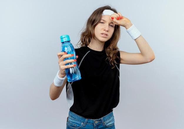 Junges fitnessmädchen in schwarzer sportbekleidung mit stirnband, das flasche wasser hält, das müde und erschöpft über weißer wand steht Kostenlose Fotos