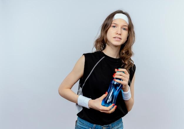 Junges fitnessmädchen in schwarzer sportbekleidung mit stirnband, das flasche wasser verwirrt steht über weißer wand Kostenlose Fotos