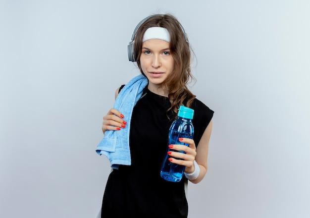 Junges fitnessmädchen in schwarzer sportbekleidung mit stirnband und kopfhörern und handtuch auf schulter, die flasche wasser hält, das sicher steht, über weißer wand steht Kostenlose Fotos