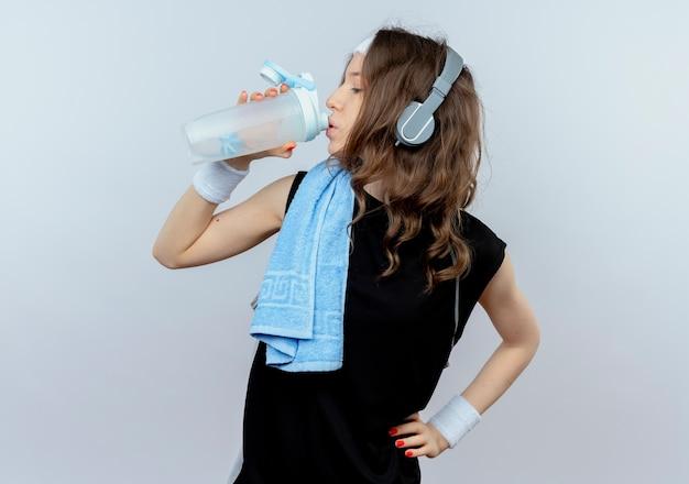 Junges fitnessmädchen in schwarzer sportbekleidung mit stirnband und kopfhörern und handtuch auf schultertrinkwasser nach dem training, das über weißer wand steht Kostenlose Fotos