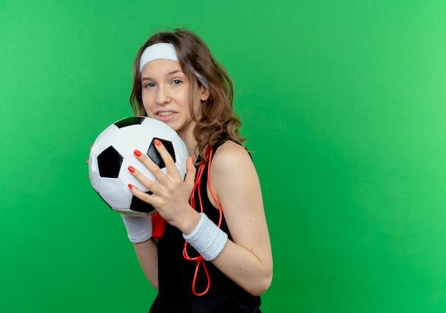 Junges fitnessmädchen in schwarzer sportbekleidung mit stirnband und springseil um den hals, der fußball lächelnd steht über grüner wand hält Kostenlose Fotos