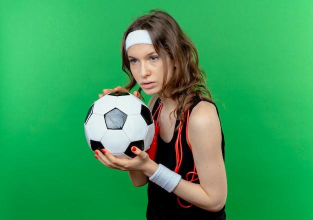 Junges fitnessmädchen in schwarzer sportbekleidung mit stirnband und springseil um den hals, der fußball schaut, der mit ernstem ausdruck über grüner wand steht Kostenlose Fotos