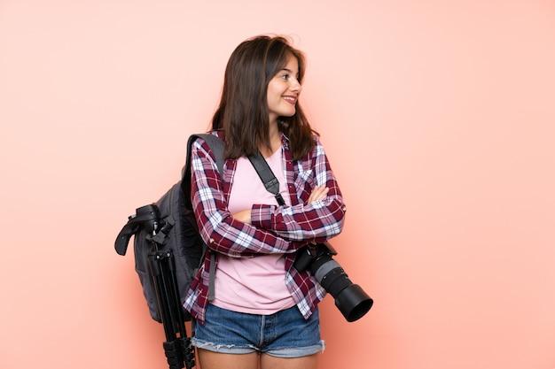 Junges fotografmädchen über der lokalisierten rosa wand, die zur seite schaut Premium Fotos
