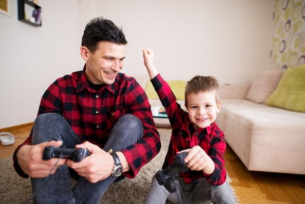 Junges fröhliches männliches kind feiert sieg in konsolenspielen, während es faust über seinem kopf hält, während sein vater ihn stolz anlächelt, während er auf dem boden sitzt. Premium Fotos