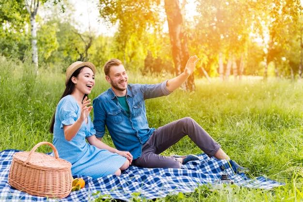 Junges glückliches paar, das auf picknick in der natur wellenartig bewegt und lächelt Kostenlose Fotos