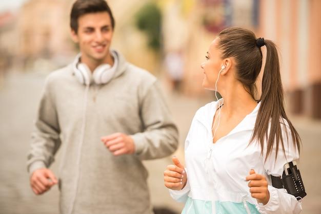 Junges glückliches paar, das draußen läuft. Premium Fotos