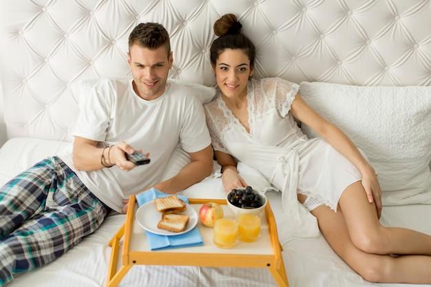 Junges glückliches paar, das frühstück im luxuszimmer hat Premium Fotos